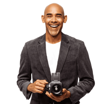 A happy man standing with his camera