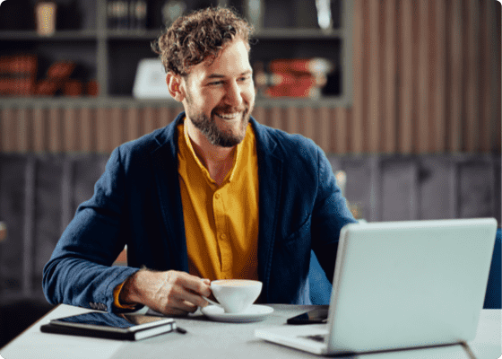 A man in blue jacket looking to laptop with coffee