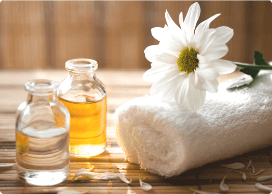 two bottles of essential oils and a towel