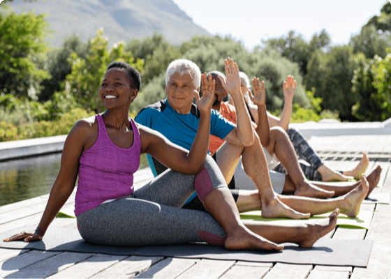 four people sitting outdoor on floor in yoga pose