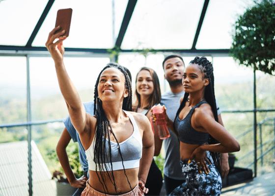 Few people posing while a woman is taking selfie