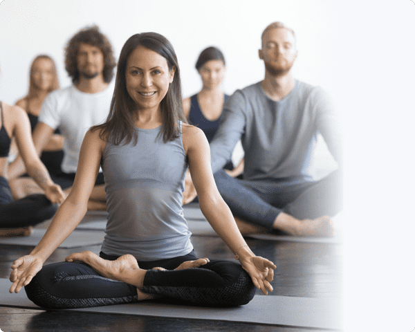 A woman in grey top leading few in a yoga hall