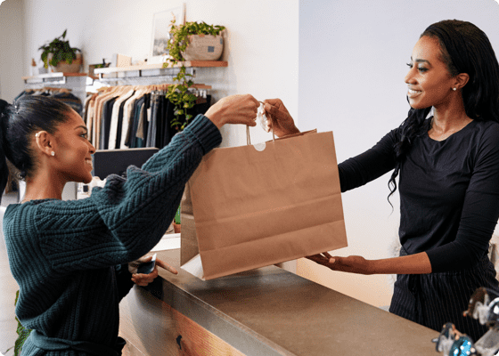 A woman handing over the bag to another in store