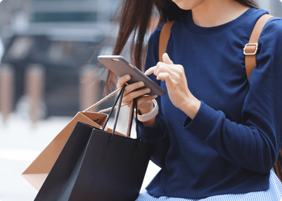 A woman operating her mobile holding shopping bags