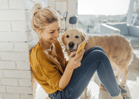 A dog reaching to a woman who is looking at mobile