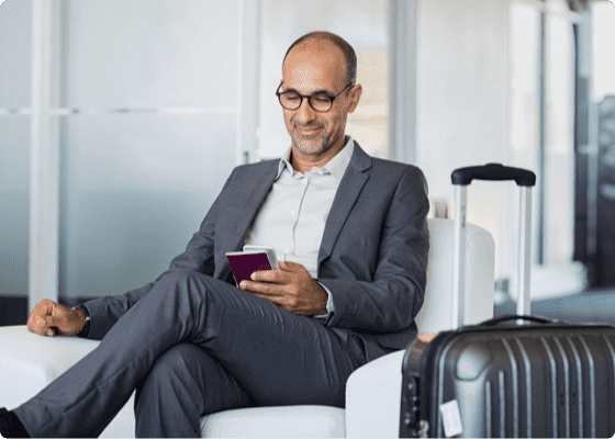 A man looking at his mobile in a waiting room