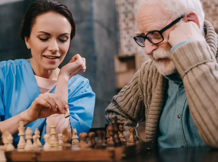 A senior man and a health care staff play chess together