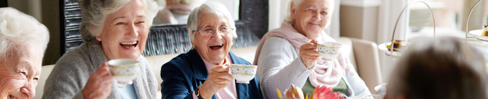 Elderly women hold up fine china tea cups and smile for the camera