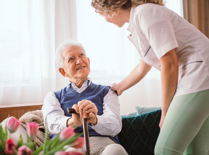 A health care worker checks in on an elderly man sitting on a couch