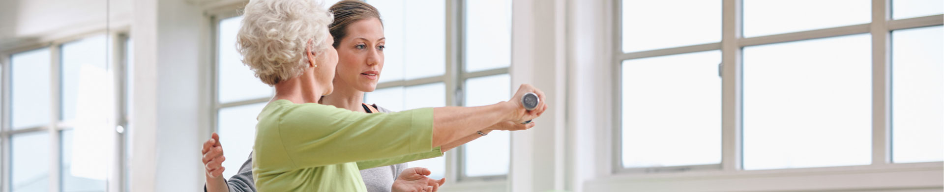 A physical therapist helps a senior woman exercise with weights