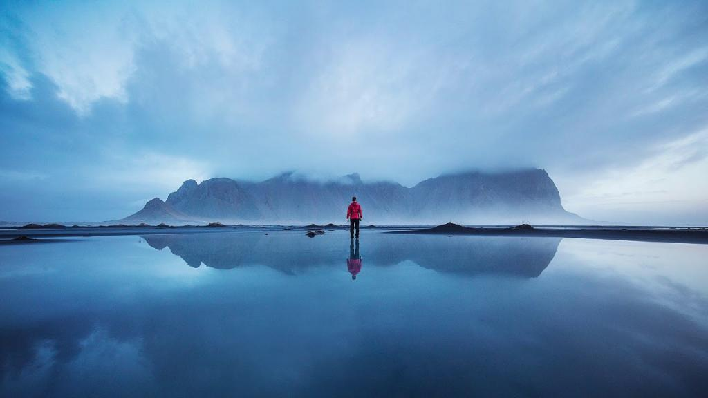 Wallpaper of a Man Walking on Water with Mountain and Clouds in Background by crenk