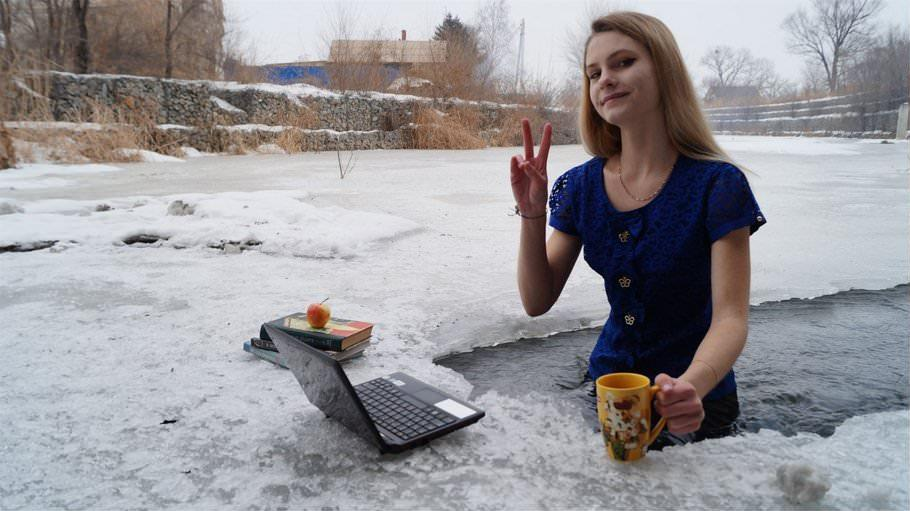 Girl Sitting in Ice Pool Outside in the Freezing Snow with Laptop of studying  by crenk