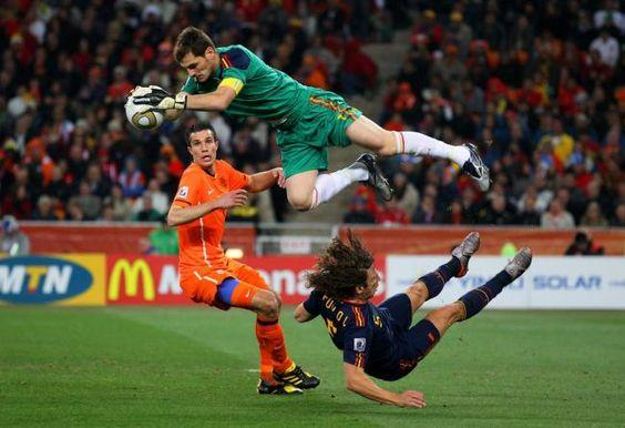 Iker Casillas of Spain catches the ball ahead of Robin Van Persie of the Netherlands as Carles Puyol of Spain falls to the ground during the 2010 FIFA World Cup South Africa Final match between Netherlands and Spain at Soccer City Stadium on July 11, 2010 by crenk