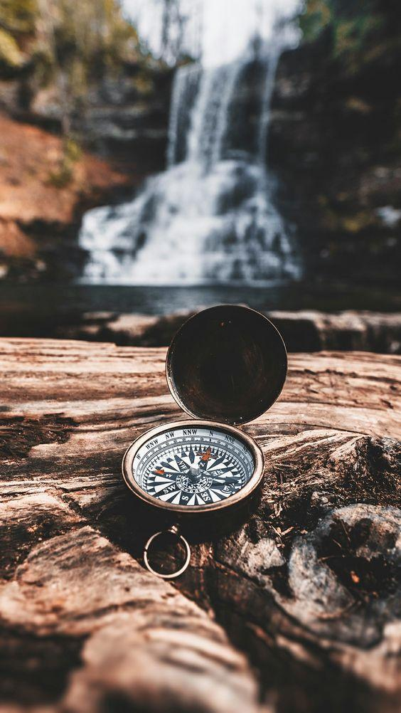 Compass sitting on the rocks in front of waterfall by crenk