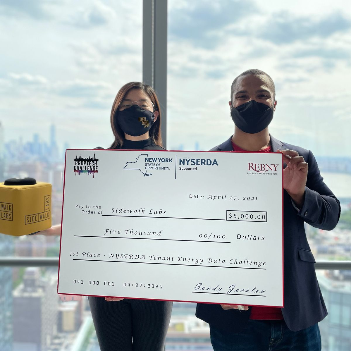 """Photograph of a woman and a man holding a large check that reads """"NYSERDA Proptech Challenge"""""""