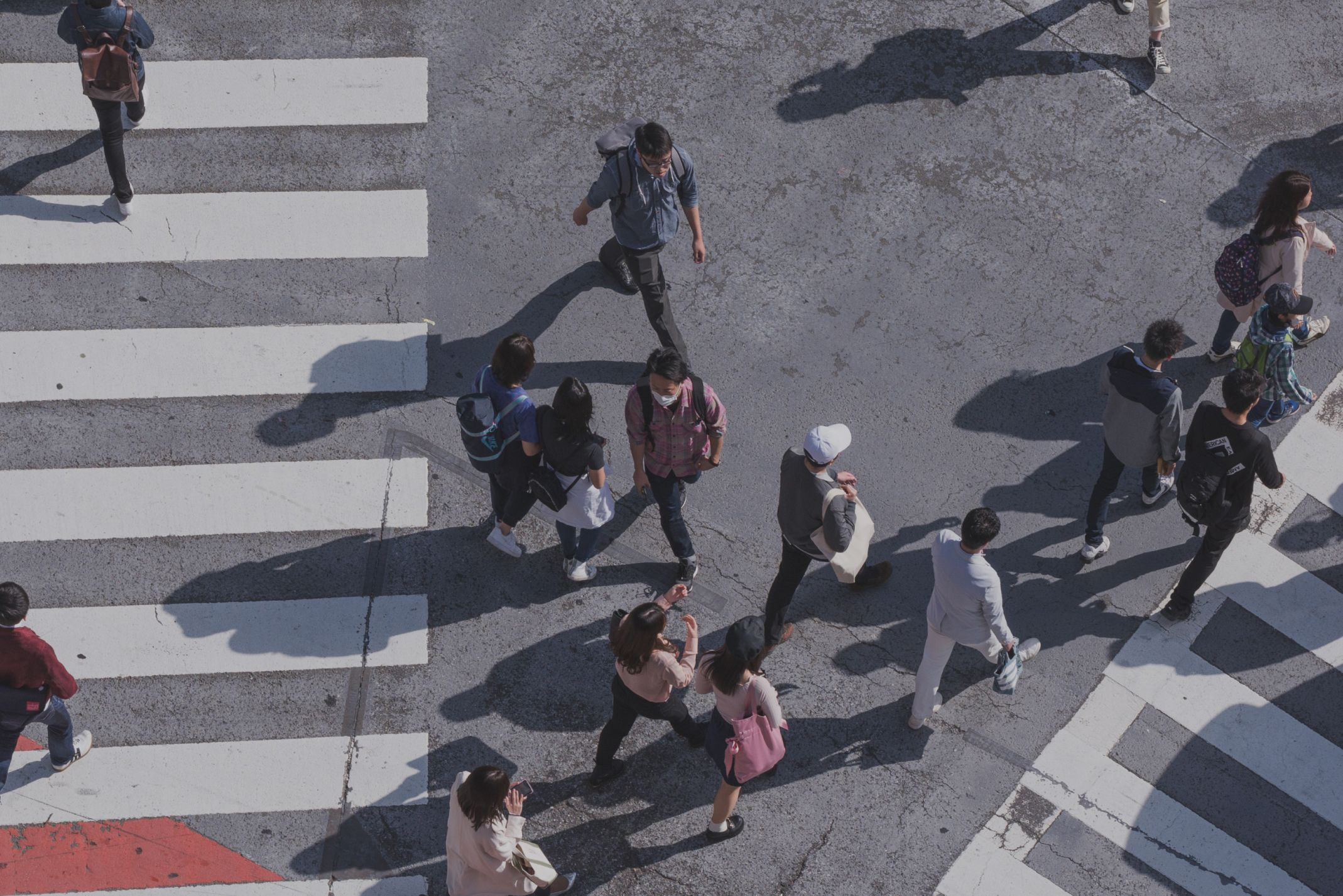 Photograph from above of people walking on a street with painted crosswalks