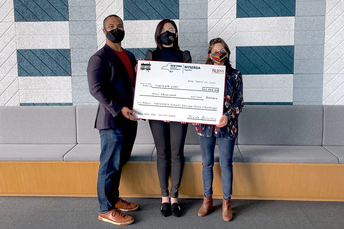 Photograph of a man and two women holding a large check.