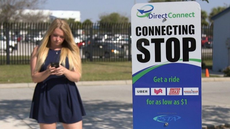 A woman waits at a DirectConnect stop