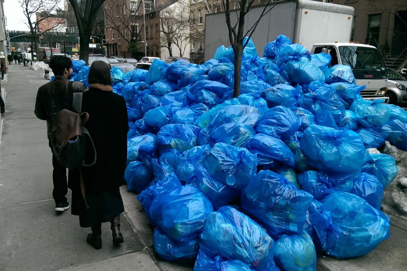 Passersby look at piles of garbage on a NYC sidewalk