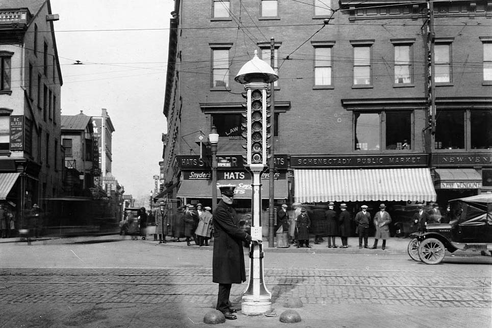 An operator stands beside an early General Electric traffic signal