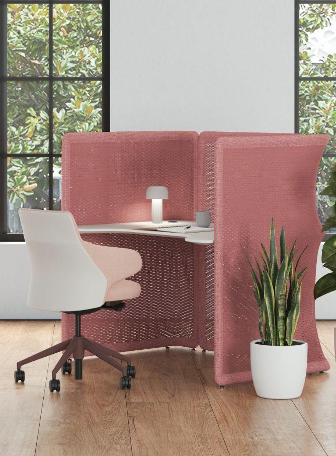 Photograph of a desk inside a stylish cubicle.