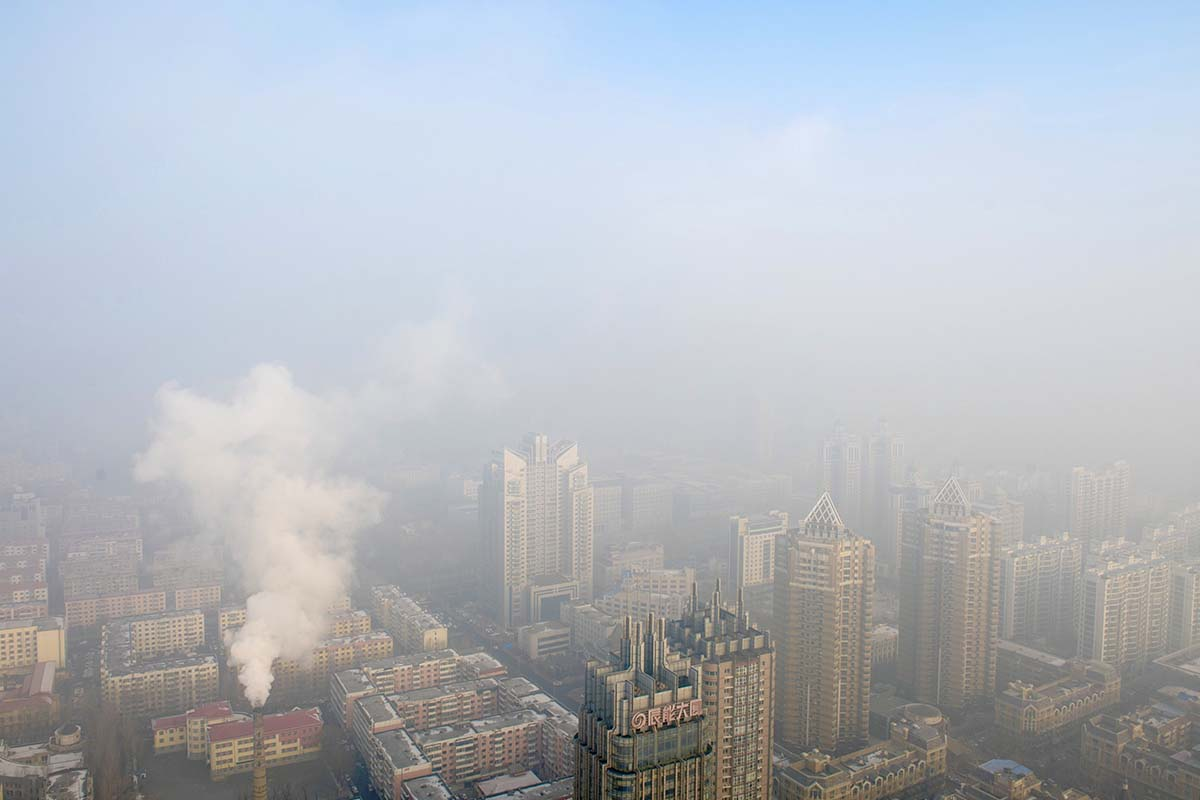 Photograph shows a city covered in smog