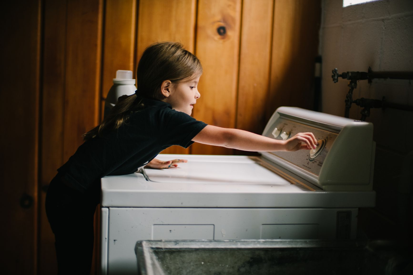 A young girl turns a knob on a washing machine.
