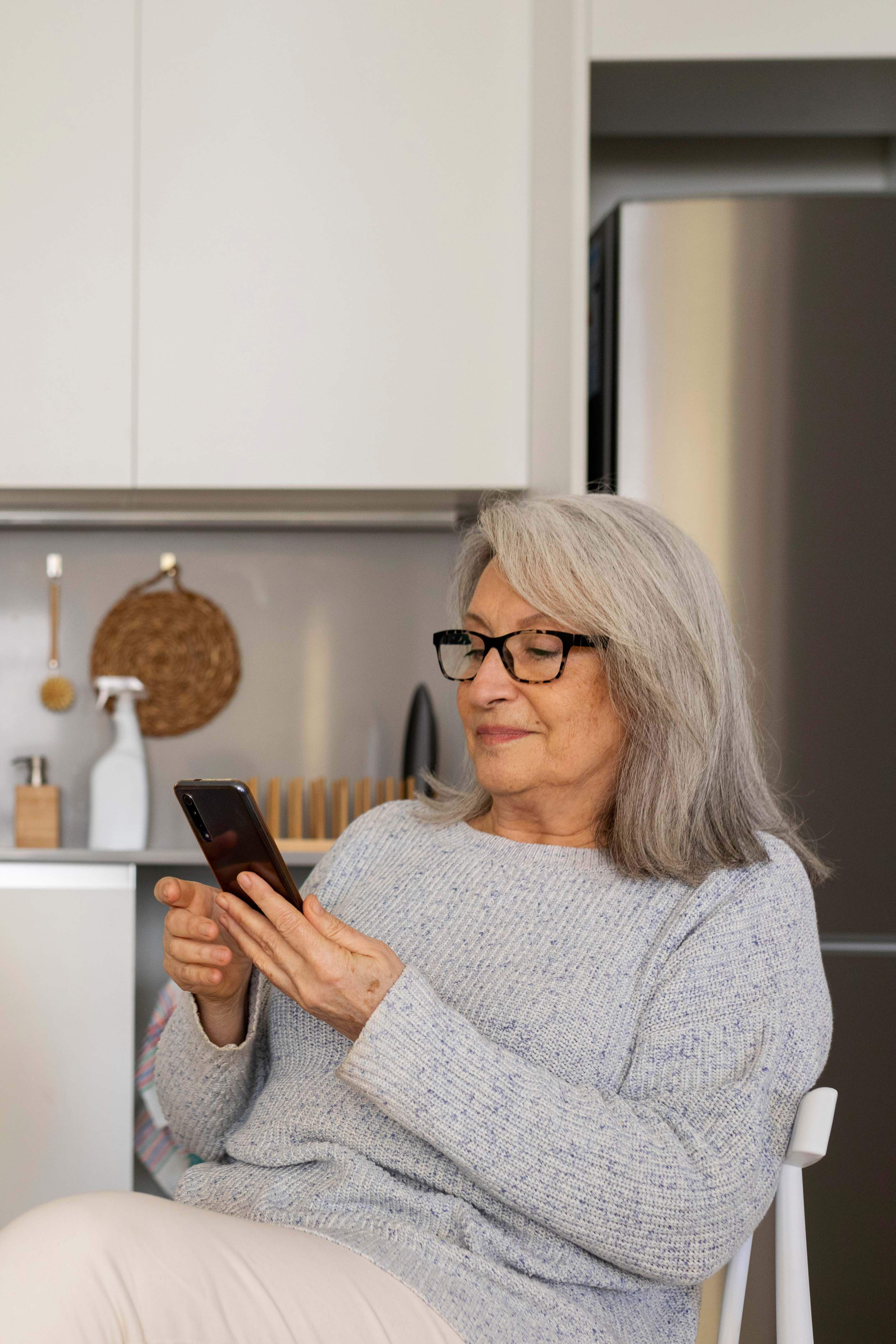 A woman is seated in her kitchen looking at her phone
