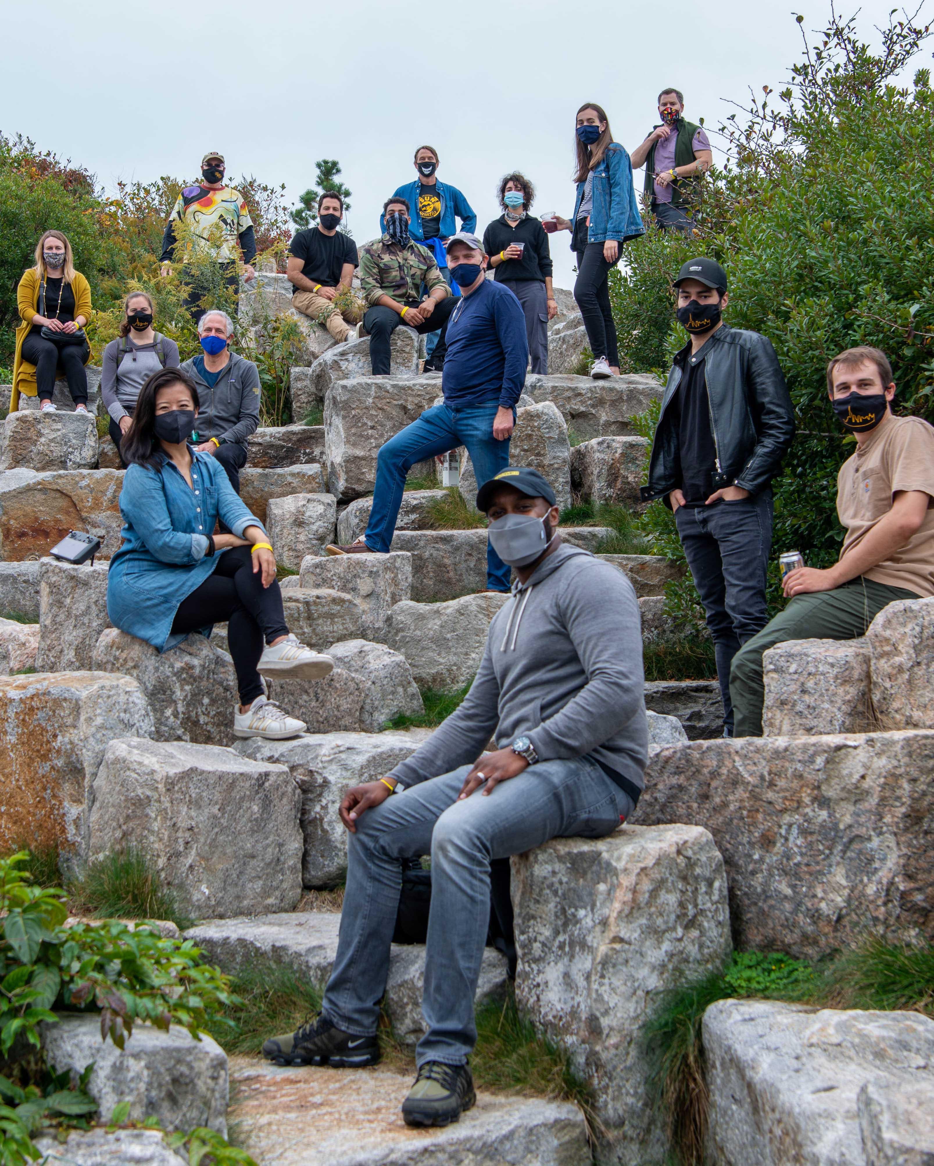Sidewalk Labs team members sit on rocks with masks.