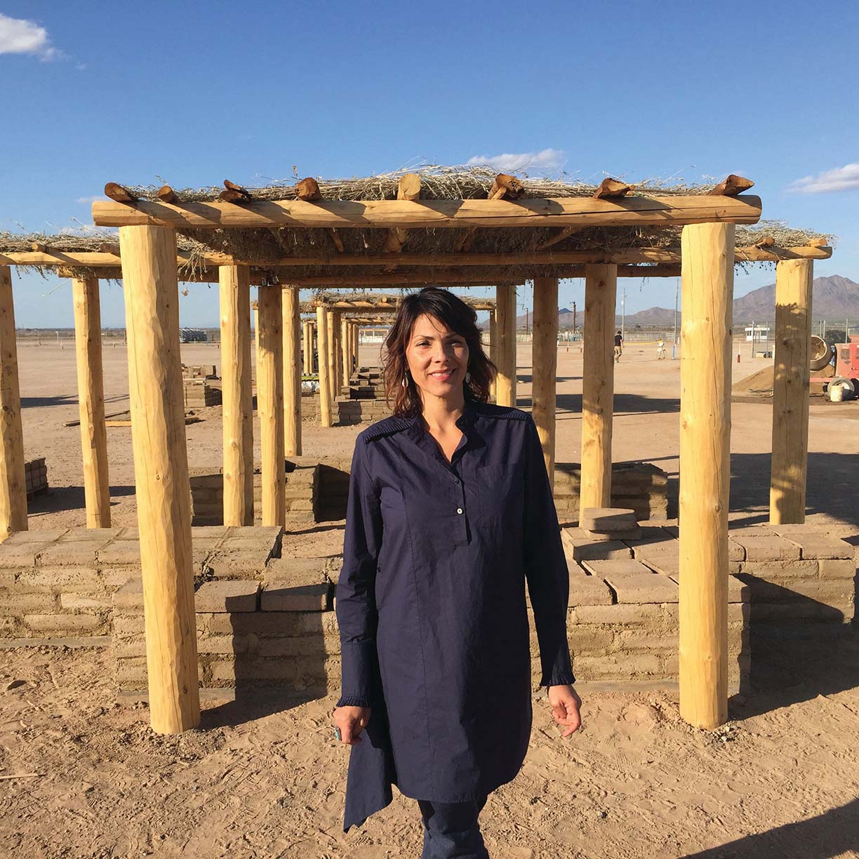 Architect Wanda Dalla Costa stands in front of a shade structure that she built for the Gila River Indian Community