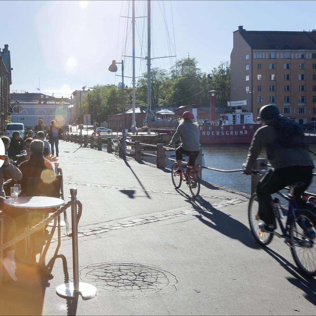 A pleasant outdoor scene with people sitting at an outdoor cafe with cyclists going by