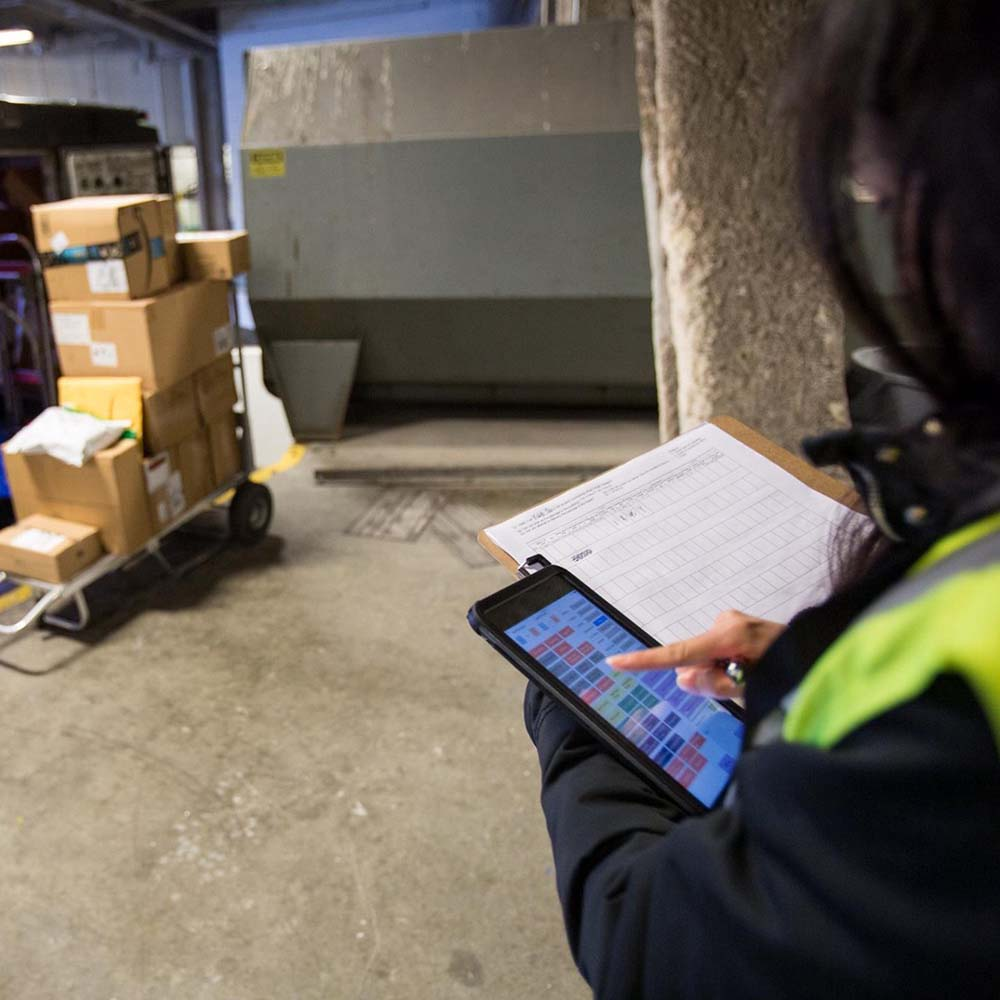 Photograph of a freight delivery room. An individual is holding tablet and inputing information.