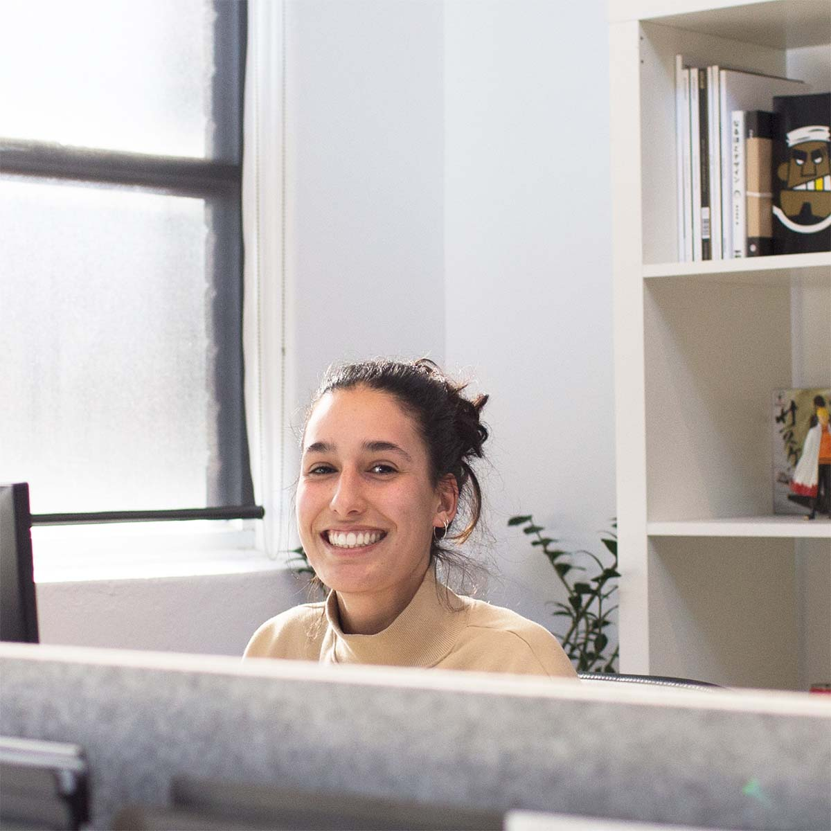 Photograph of a smiling worker in an office cubicle