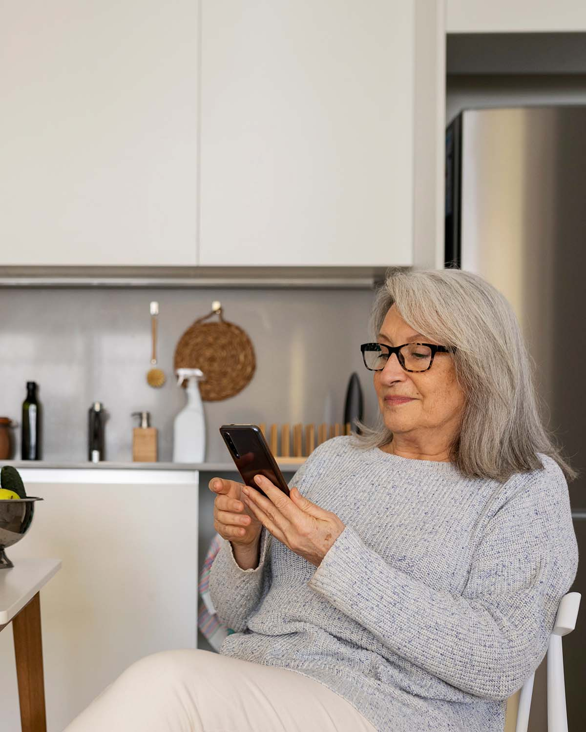 A woman sits in her kitchen and looks at her phone