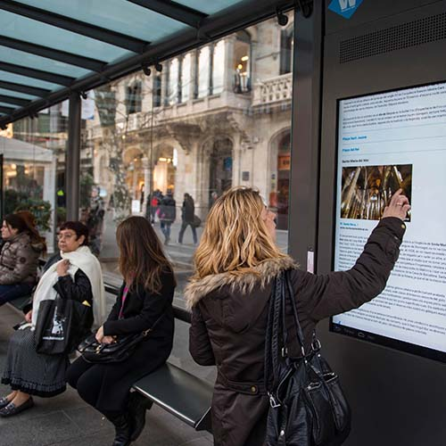 A woman reads a digital display in a train station