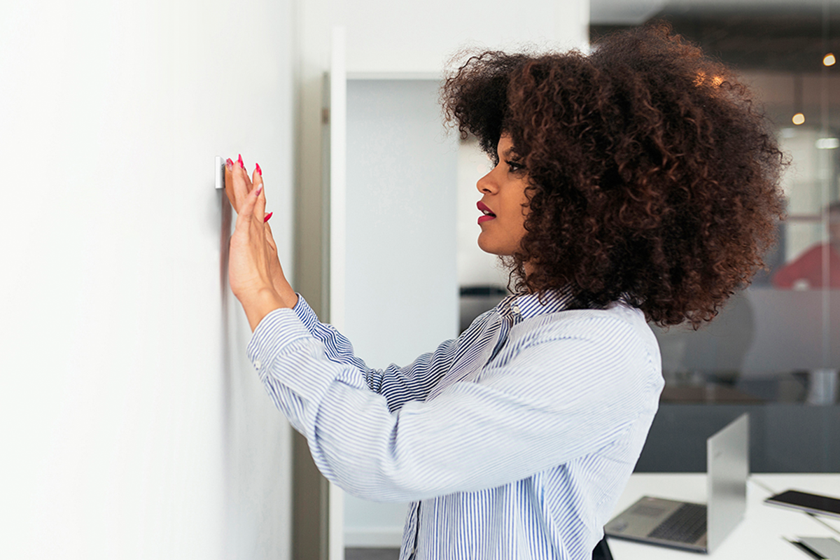 A woman presses a Mesa sensor on the wall