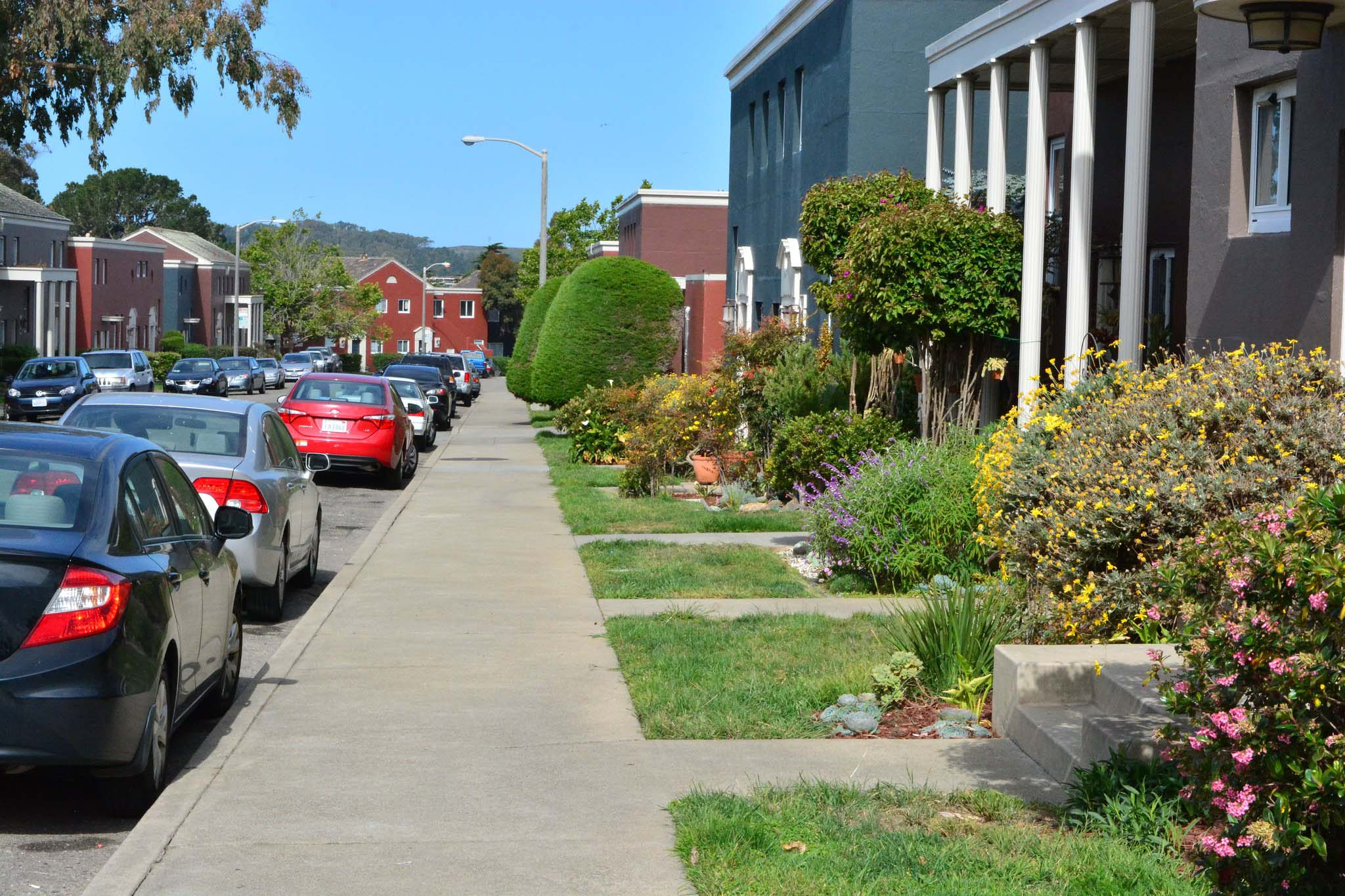 A sidewalk, homes, and cars in the Parkmerced development in California.