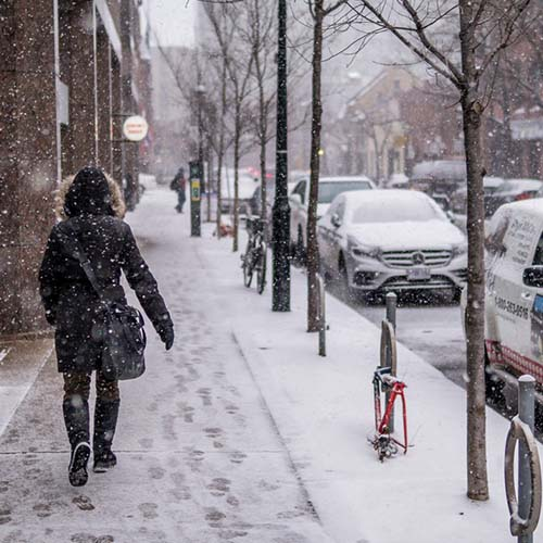 A woman walks down a snow-covered sidewalk