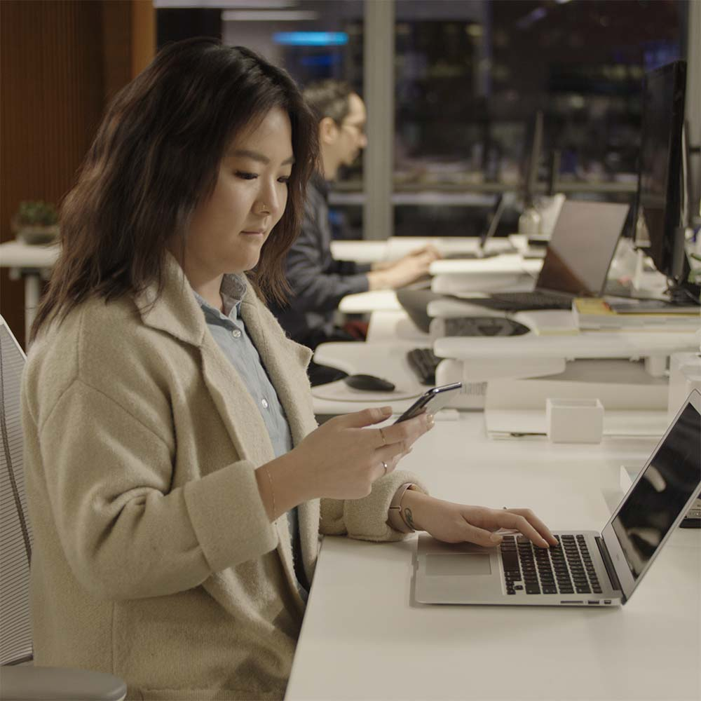 Photograph of a worker using her phone and her laptop