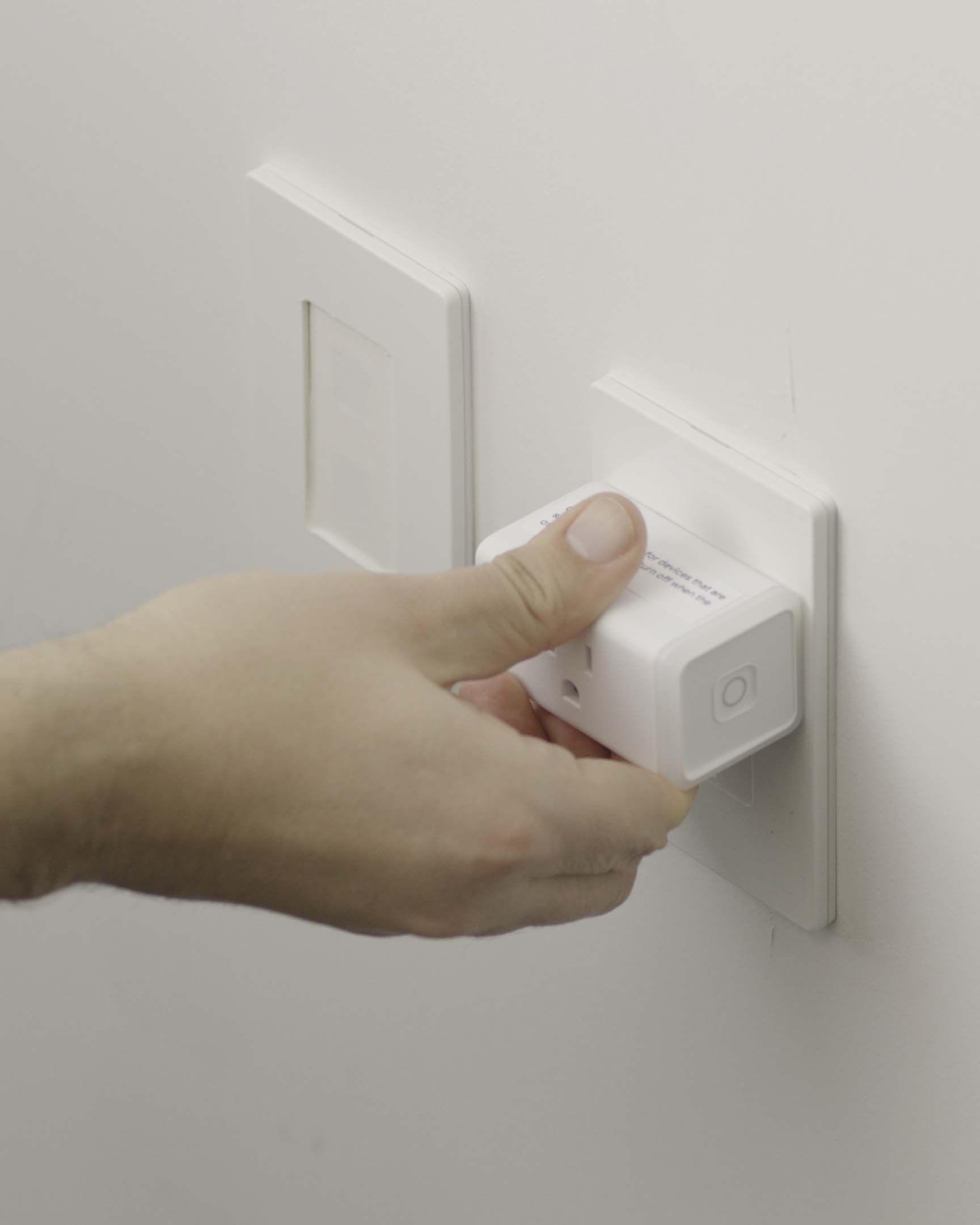 A hand plugging in a Mesa smart plug