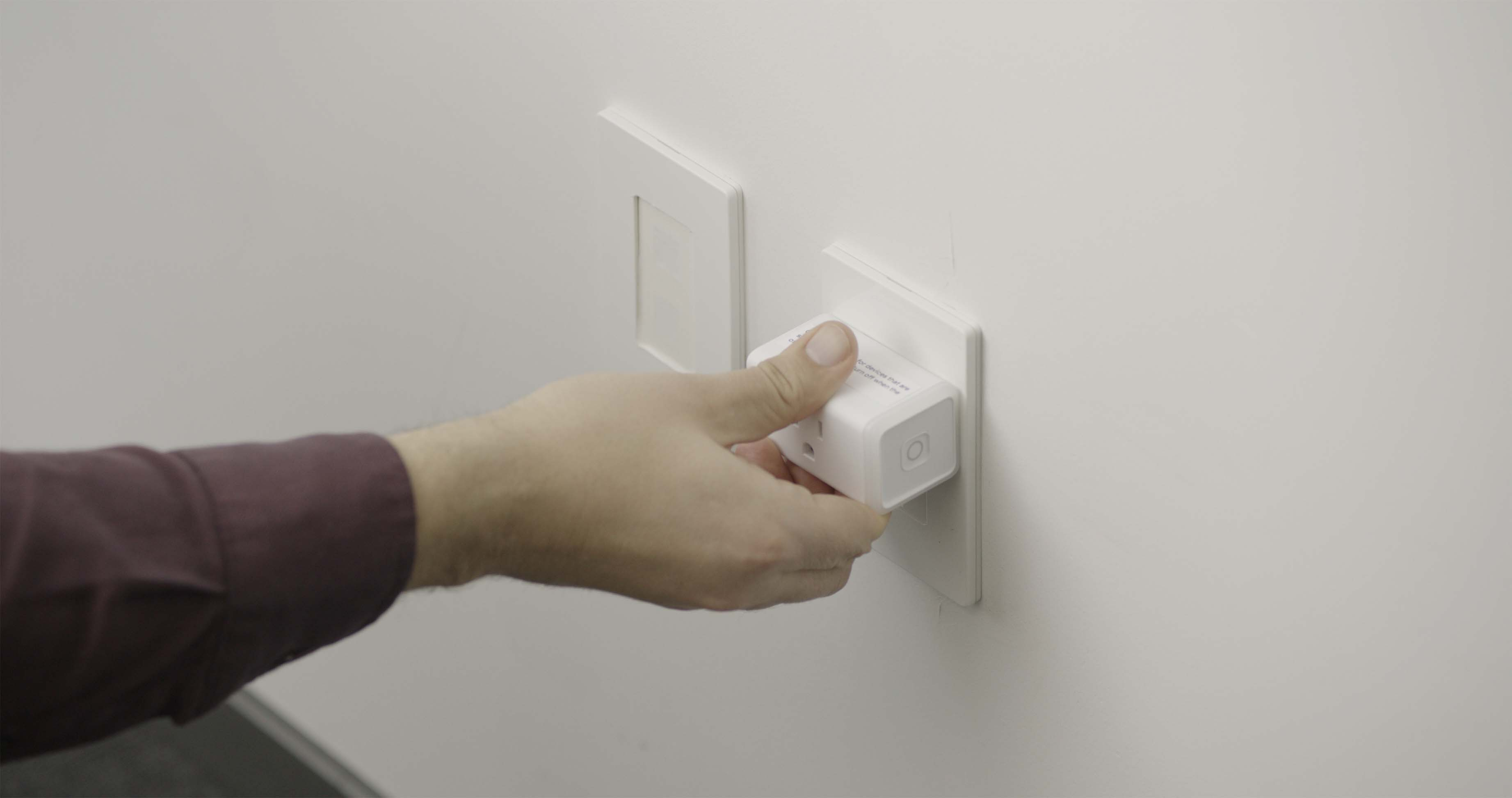 Photograph of a person plugging a smart plug into a wall outlet