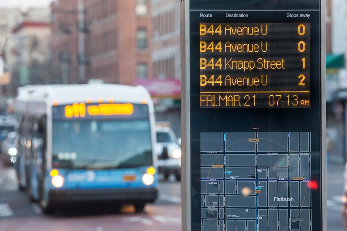 A bus pulling up at a real-time transit arrival screen