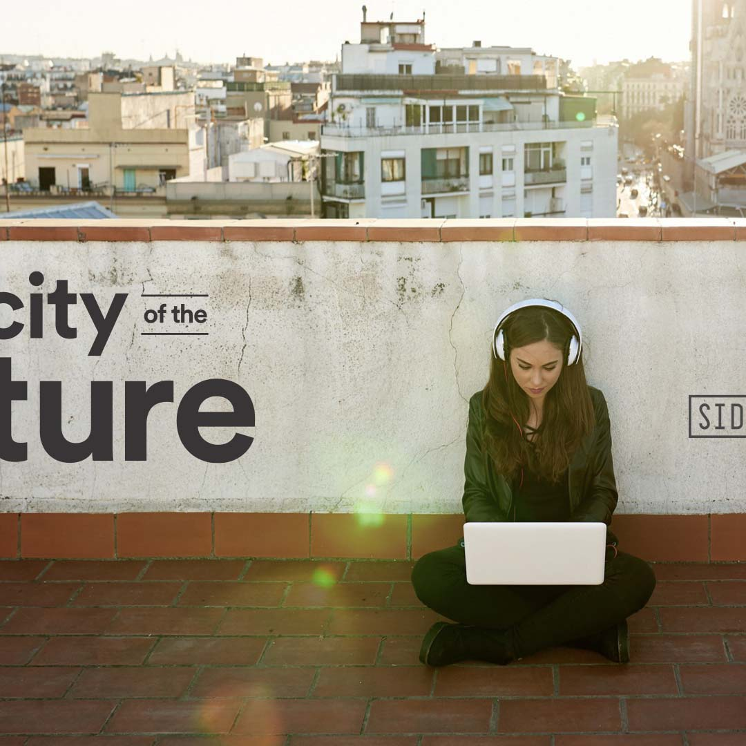 A woman sits outside working on a laptop with headphones on