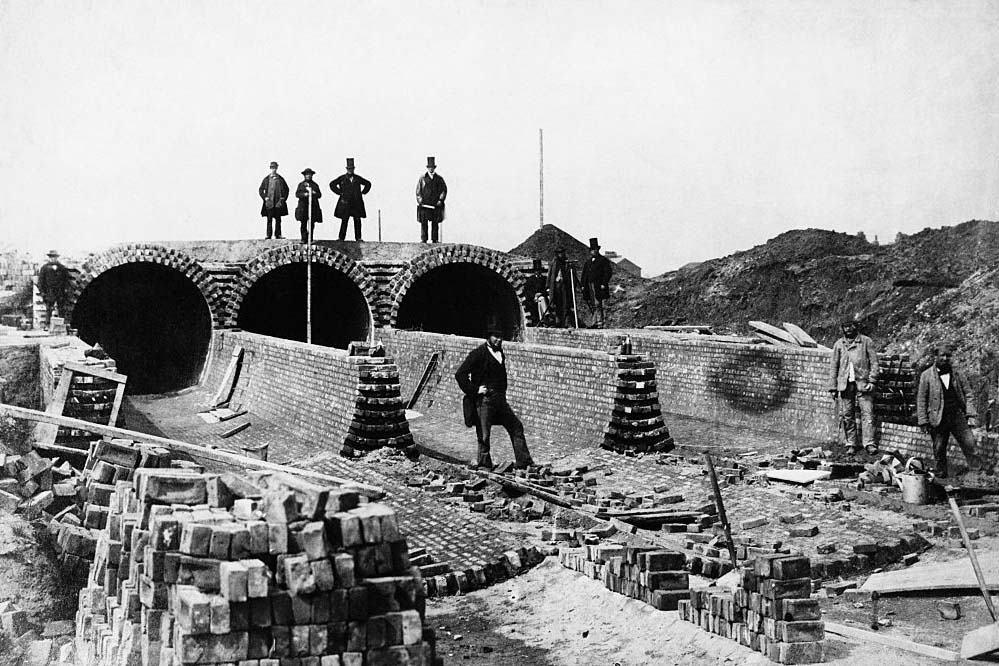 Men standing near the Northern Outfall Sewer