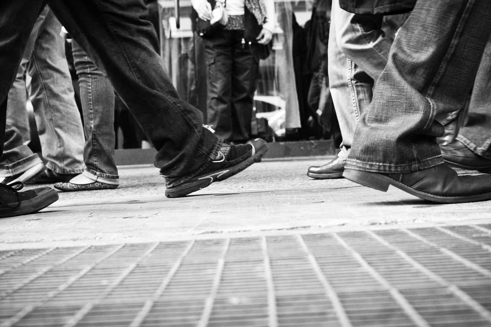 Black and white photo of people walking on a sidewalk