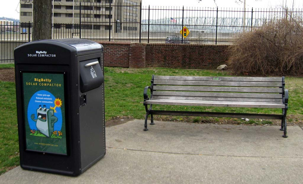 A BigBelly waste receptacle next to a park bench