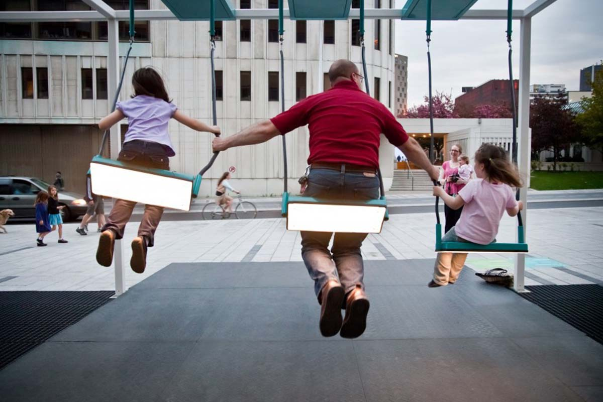 A family plays on a swing set