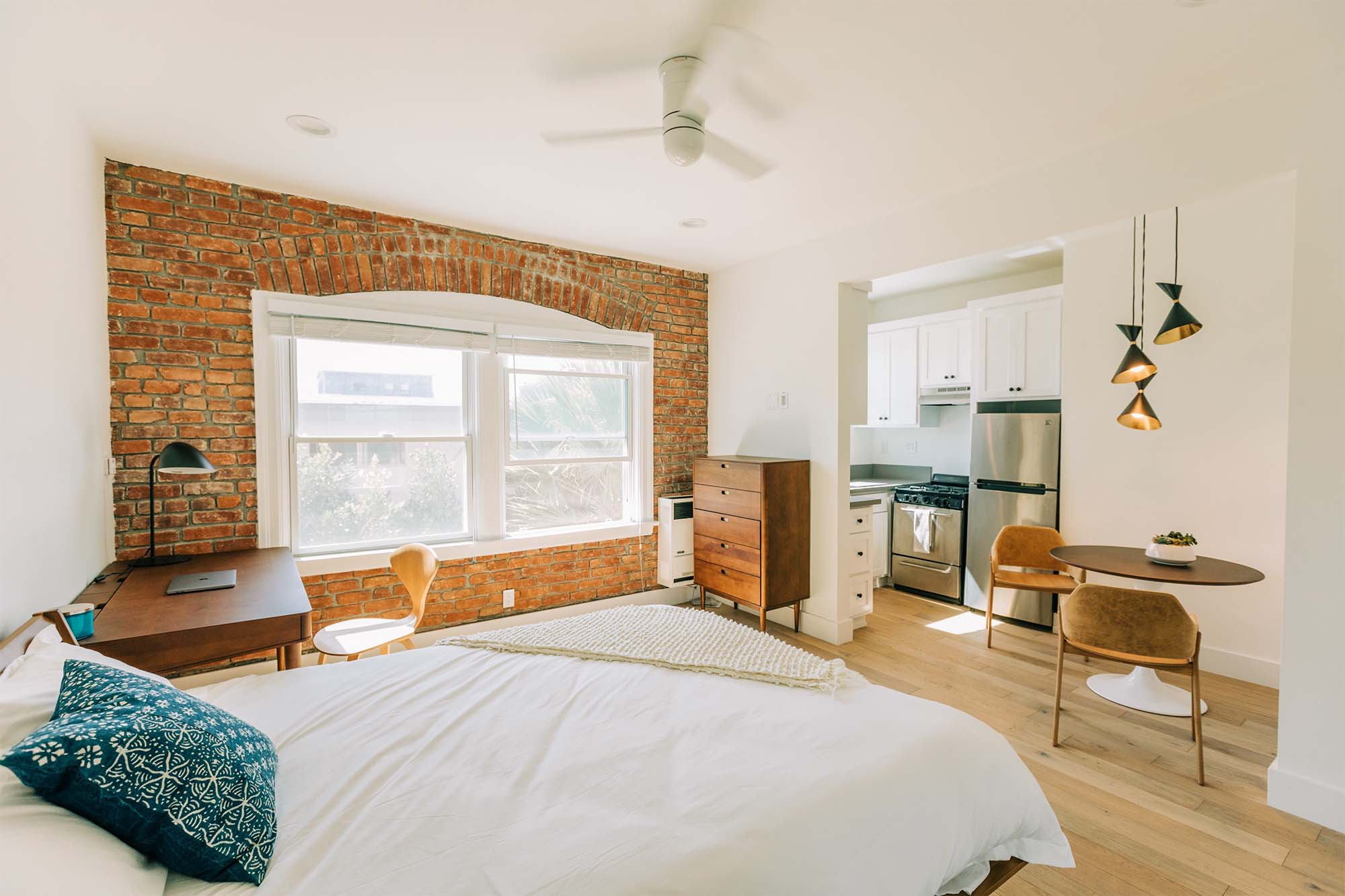 Photo of an airy apartment with a bed, desk, and chair. In the back you can see the entrance to a kitchen.