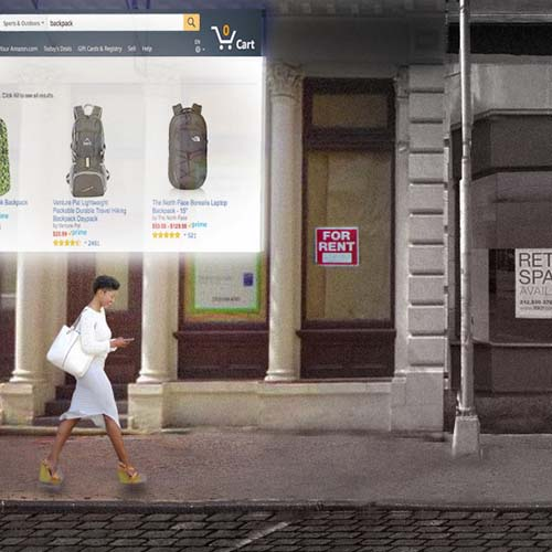 A woman walks past several empty storefronts