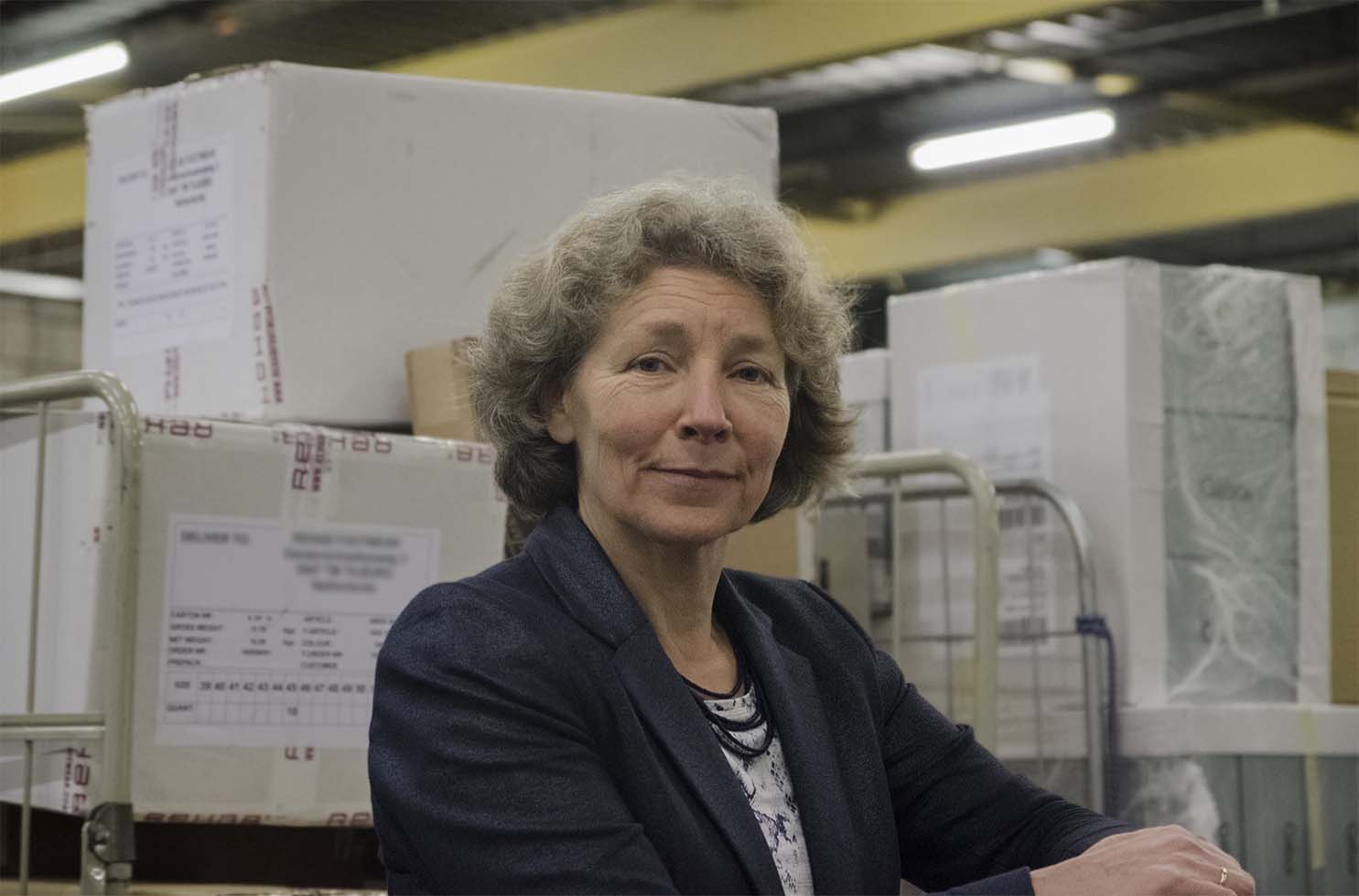 A photo of Birgit Hendriks in a delivery warehouse in front of packages.